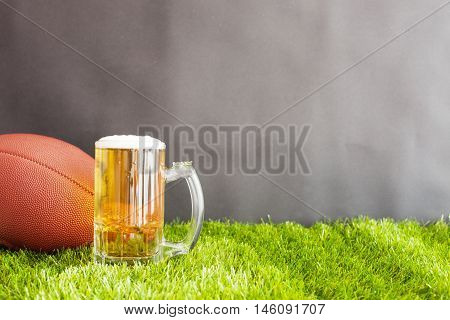 Vintage football and beer jar over grass