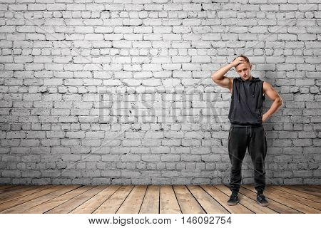 Front view of muscled young man thinking, on the background of white brick wall. Wellbeing. Muscleman. Workout and fitness.