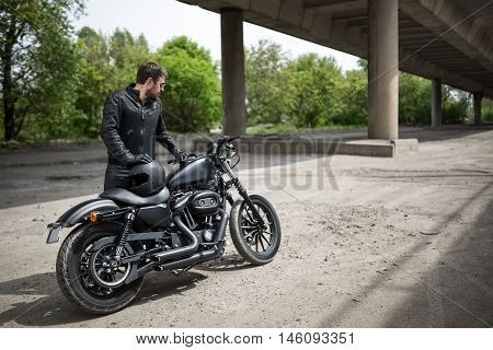 Bearded man stands near his black motorcycle on the dirt road under the overpass on the nature background. He holds his left hand on the motorcycle and right hand on the black helmet. He looks to the left.