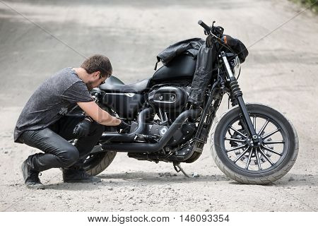 Brutal man with a beard checks his black motorcycle on the dirt road. He sits on his haunches and looks inside the motorcycle. He wears black jeans, a dark-gray T-shirt with a print, black shoes, black gloves and sunglasses.