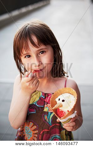 Cute girl eating ice-cream outside on summer sunset