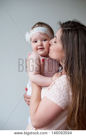Happy Mother Kissing Her Smiling Baby