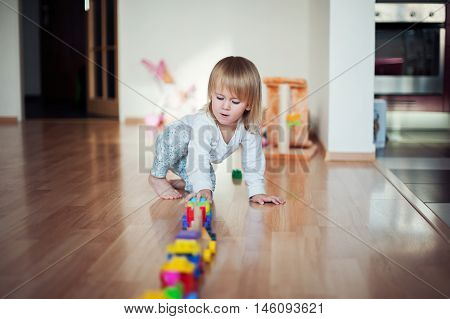 Little girl playing with train. Toddler kid play with trains and cars. Educational toys for preschool and kindergarten child. Girl build toy railroad at home or daycare.
