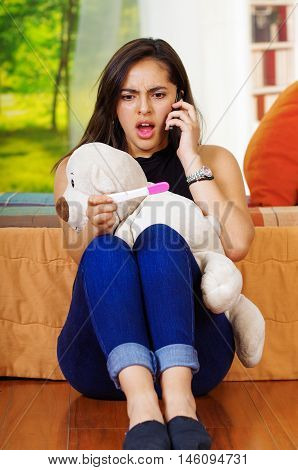 Pretty young brunette woman holding pregnancy home test, talking on phone and looking shocked, teddybear in lap, garden window background.