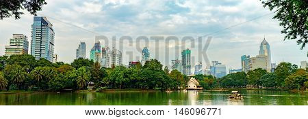 Panorama of Bangkok skyline from Lumphini Park Thailand. Business district cityscape from a park with cloudy sky in the evening with reflection.