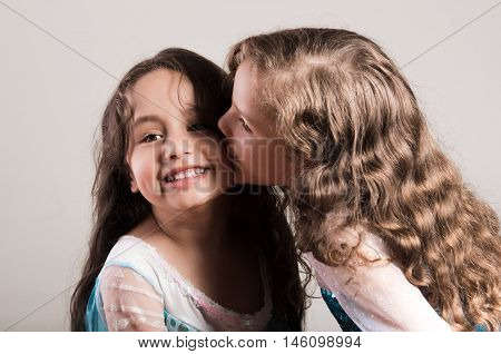 Adorable big sister kissing sibling on cheek, both wearing matcing blue dresses posing together happily, studio background.
