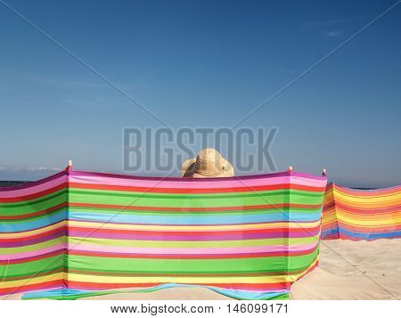 Female sunbather in straw hat relaxing on the beach behind windbreak