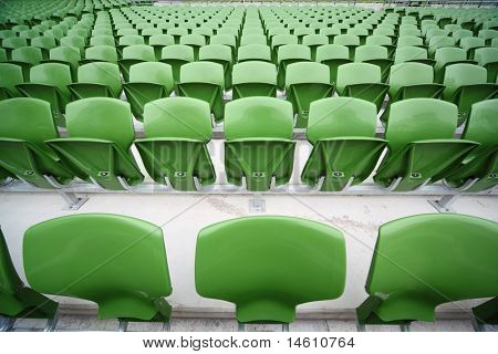 Rows of folded, green, plastic seats in very big, empty stadium. Focus on front seats