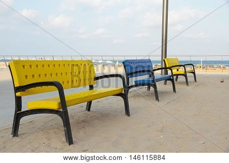 three colorful benches in a rest area on the beach