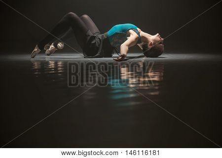 Ballerina in the ballet suit lying on the floor with arched back and outspread arms. She is reflected on the floor surface. Light falls on her body from above. Shoot in a low key.