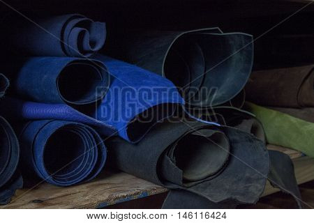 Blue and black rolls of leather sit on a shelf.