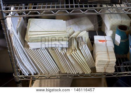 Handmade paper in varying sizes sits on a shelf.