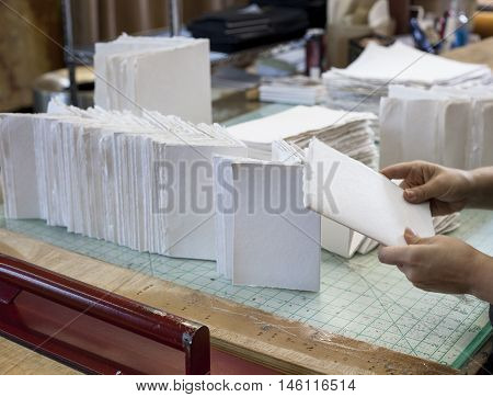 A worker folds hundreds of newly cut homemade paper pages.
