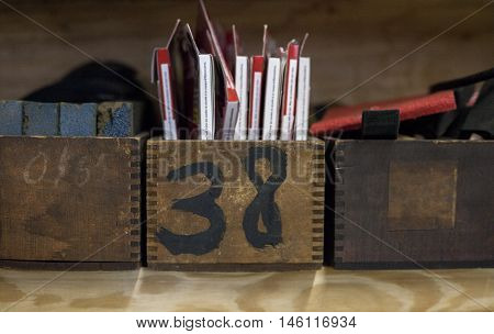 Antique boxes sit on shelf with various items inside and one is labeled with the number 38.