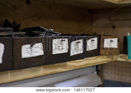 Labeled boxes sit on a shelf inside a bookbinders studio.