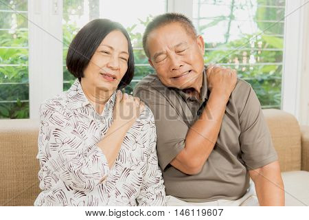 Senior asian couple having back and neck pain problem.