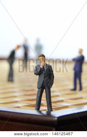 Business man figurine standing on a scrabble game board looking out.