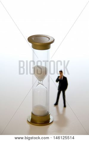 Business man figurine standing and looking at a sand timer.