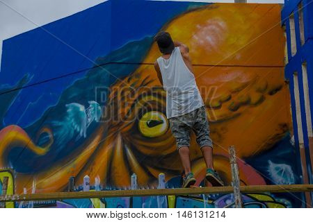 PUNTA DEL ESTE, URUGUAY - MAY 06, 2016: young man finishing a grafitti painted in the wall.