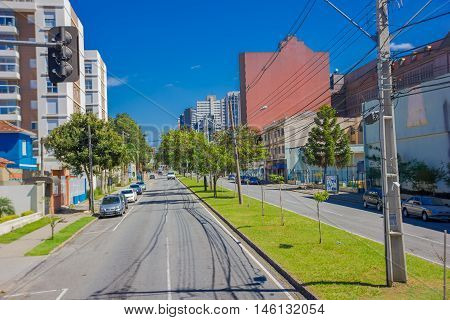 CURITIBA , BRAZIL - MAY 12, 2016: long empty street with some autos parked at the sides and some trees on the sidewalk.