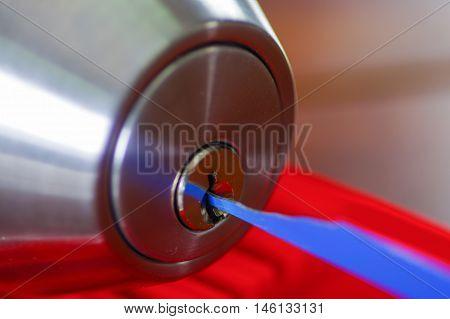 Closeup hands of locksmith using metal pick tools to open locked door.