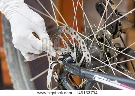 Closeup hand wearing white glove using black unbrako tool unscrewing cogwheel parts of bicycle wheel, mechanical repair concept.