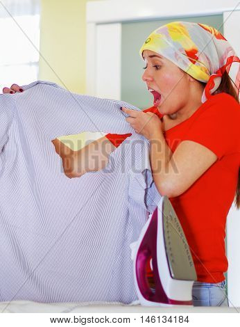 Young charming woman wearing colorful headscarf holding up office shirt with hole bruned through fabric, shocked facial expression, laundry housework concept.