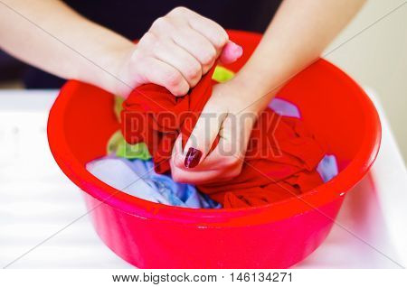 Closeup womans hands handwashing clothes in red plastic washbucket, scrubbing and squeezing fabrics, laundry housework concept.