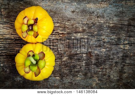 Top view. Two garcinia cambogia fruit on wood background and free form copy space. Garcinia atroviridis is a spice plants and hydroxy citric acids (HCA) for good health.