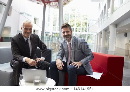 Portrait Of Businessmen Meeting In Lobby Of Modern Office