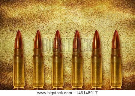 Six shiny bullets on grunge background arranged vertically