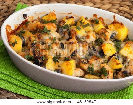 Casserole dish with potatoes chicken breasts olives and fresh herbs. Horizontal shot