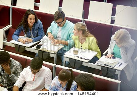 education, high school, university, learning and people concept - group of international students with notebooks talking at lecture hall  (shot through glass)