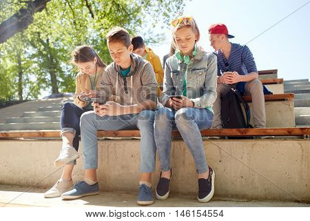 technology, internet addiction and people concept - group of teenage friends or high school students with smartphones outdoors