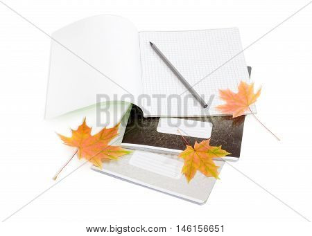 Open the first page school exercise book with sheets of squared paper pencil other exercise books and several yellowed maple leaves on a light background