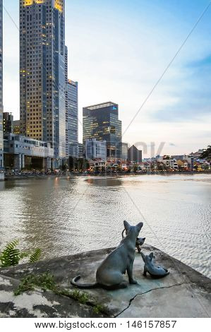 SINGAPORE, REPUBLIC OF SINGAPORE - JANUARY 08, 2014: Sculpture Cat with kittens on the Singapore river embankment at twilight