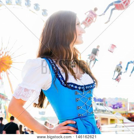 Dirndl wearing woman is standing in front of ferris wheel and carousel at Bavarian folk festival
