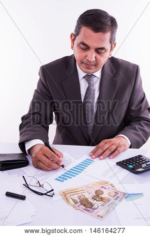 Indian man or accountant person filing Indian income tax returns form or ITR document showing indian currency, house model, toy car and calculator over white table top, selective focus