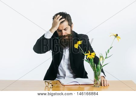 young handsome bearded man scientist or professor with long beard and teacher glasses with pencil and book or notepaper near yellow flowers sitting at table isolated on white background