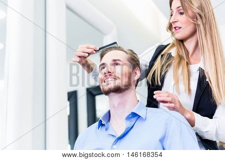 Haircutter cutting hair of customer