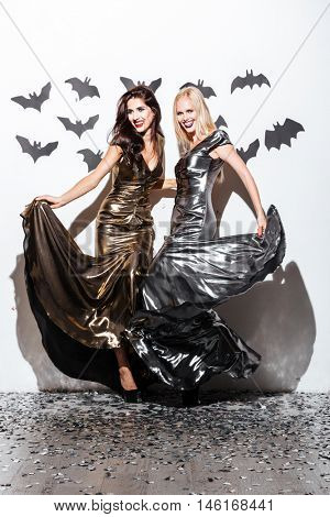 Full length of two cheerful young women with halloween vampire makeup on party over white background