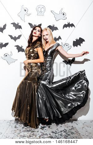 Full length of two attractive young women with gothic vampire makeup on helloween party over white background