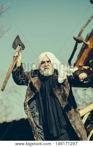 Brutal druid old man with long silver hair and beard in fur coat with axe in hand on blue sky background