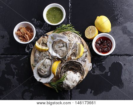 Fresh Oysters on table with lemon and side dish
