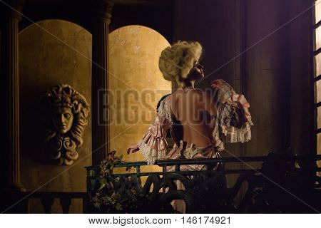 Half-naked Victorian lady. Young woman in eighteenth century image posing in vintage interior