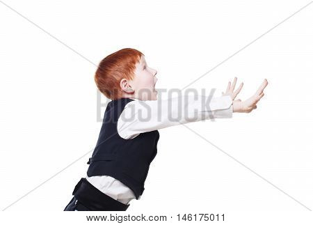 Little cute redhead boy in balck vest side view profile portrait, stopping something with hands, shouting scared. Portrait of well-dressed sweet child in bow tie isolated on white background