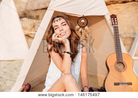 Beautiful brunette hippie girl sitting at the tent with eyes closed at beach