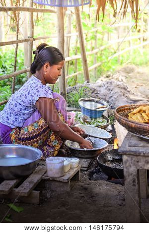 MANDALAY, MYANMAR - DECEMBER 2015: A female Burmese makes fried Bagan sweet potato, a common snack in a village by Irrawaddy river of Bagan. Bagan, an ancient town in Mandalay, Myanmar.