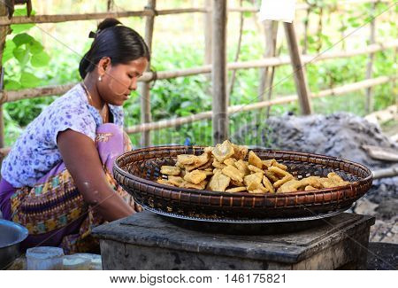MANDALAY, MYANMAR - DECEMBER 2015: Bagan fried sweet potato made fresh by a Burmese villager in a small village by Irrawaddy river of Bagan. Bagan fried sweet potato is a common snack in Bagan area. Bagan, an ancient town in Mandalay, is the most visited