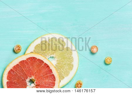 Top view on cut red and yellow grapefruit and small citrus candies on white wooden background. Juicy and fresh fruit. Healthy eating concept. Flay lay.
